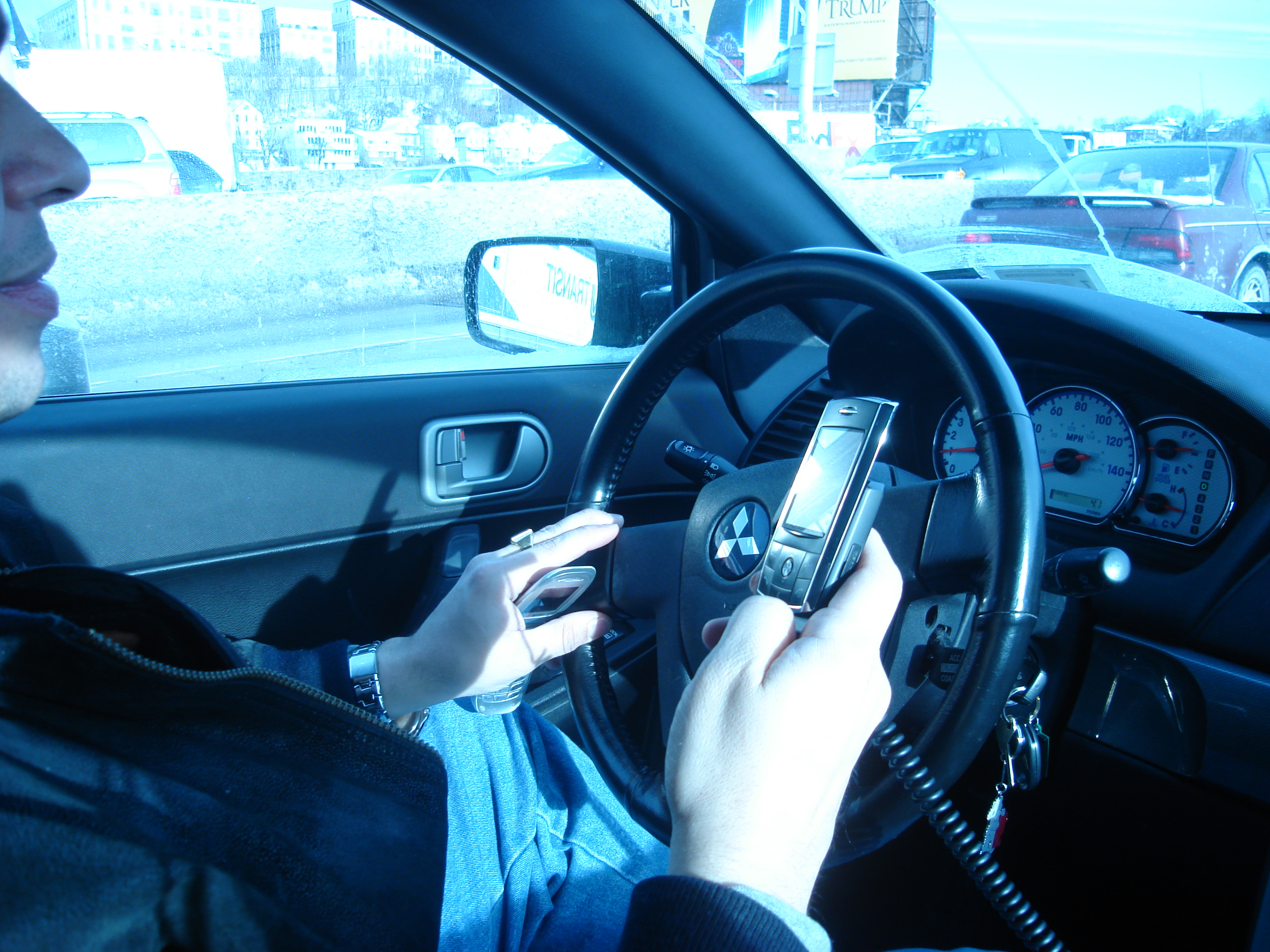 A New York City driver using two handheld mobile phones at once.