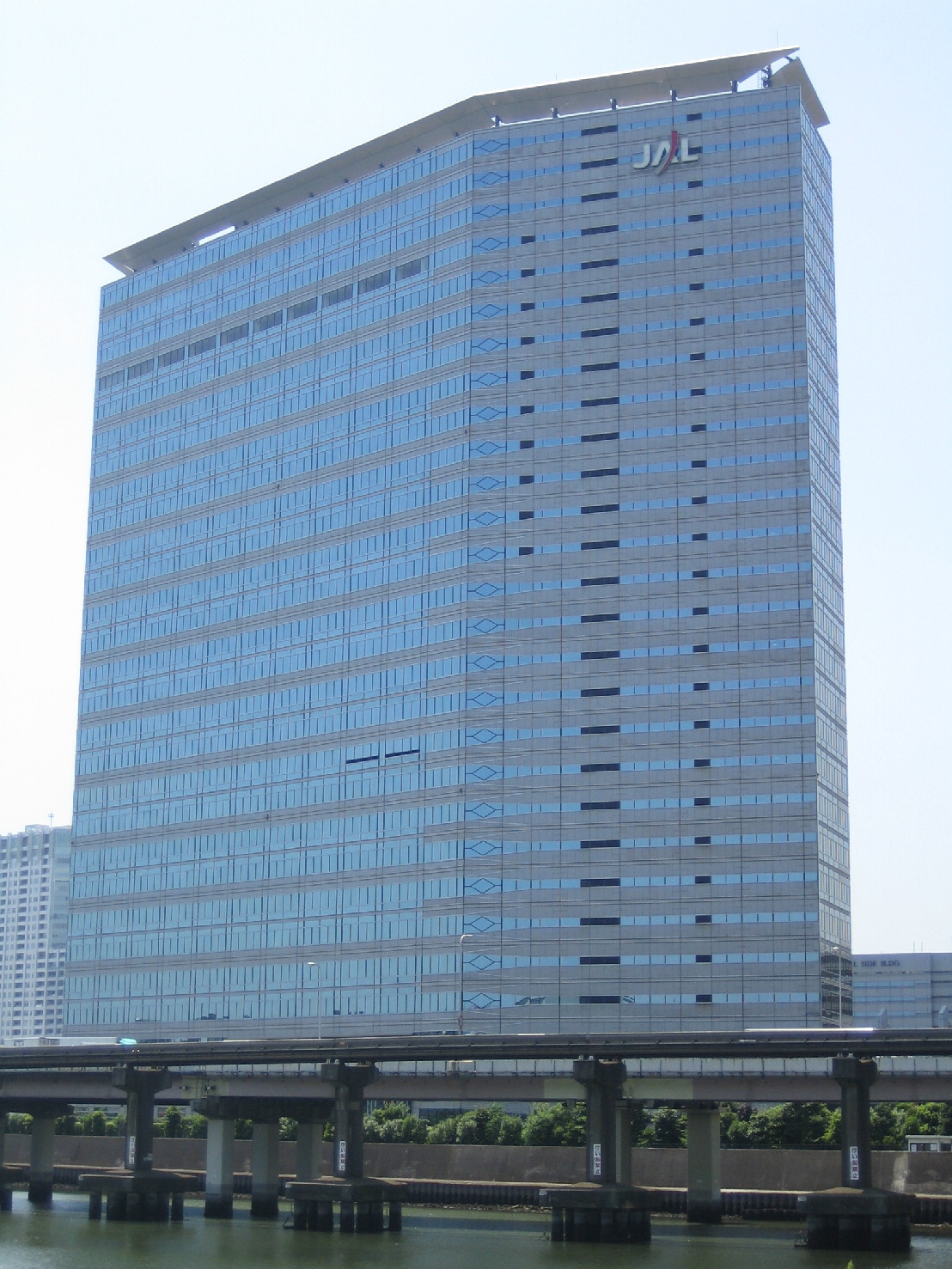 "A modern multi-storey building in blue and grey colour, with Japan Airlines' ""JAL"" logo on the top right, there are blue sky on the background and a highway bridge in the foreground"
