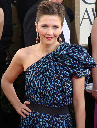 A woman with brown hair poses with her hand on her hip. She is wearing a one-shouldered green and black dress, with long gold earrings, and her hair is styled and tied back.
