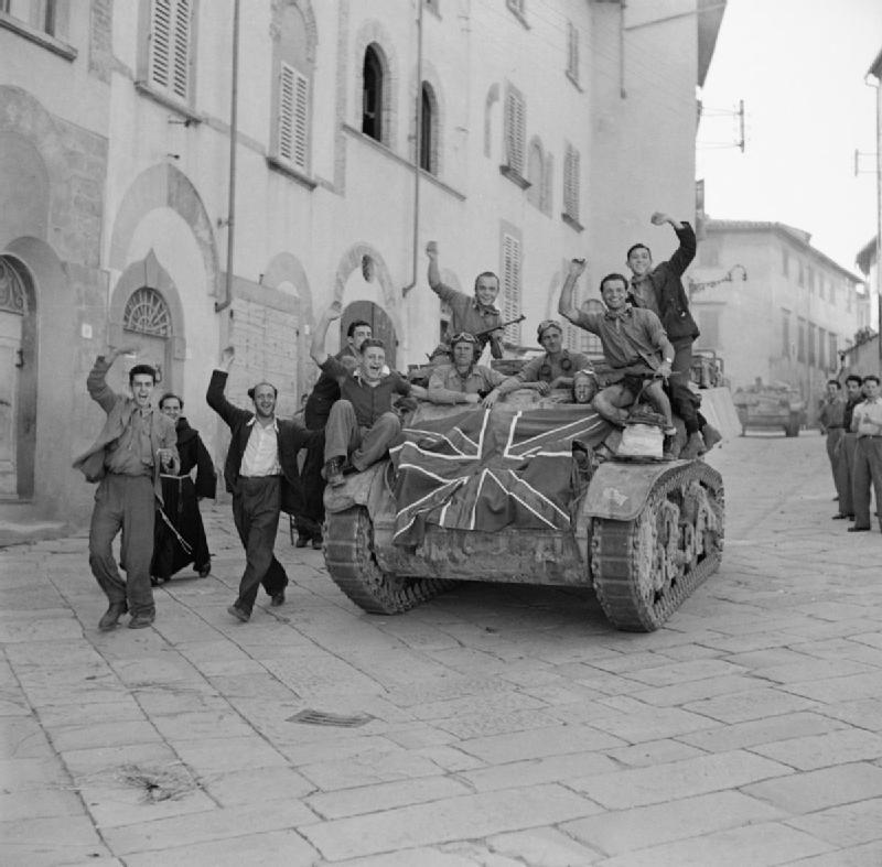 Italian civilians clamber aboard a turretless Stuart