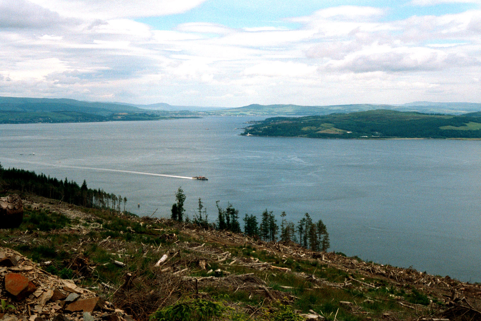 The inner firth seen from the Cowal peninsula near Dunoon, looking north east to the coast of Inverclyde at Cloch point south of Gourock and Greenock, and beyond that the Tail of the Bank. <!-- ship --> can be seen cruising south