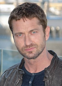 Headshot of Gerard Butler facing the camera with short brown hair and trimmed beard