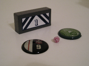 Typical ball, buttons, and goaltender game pieces