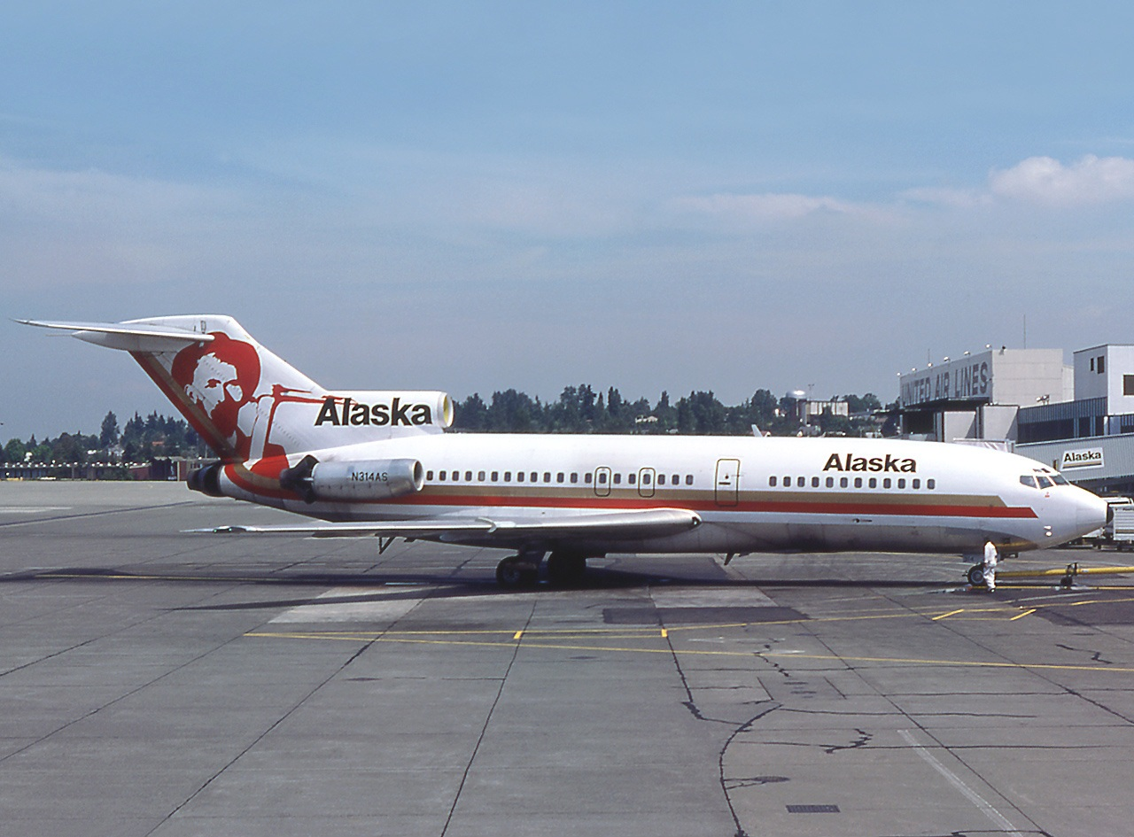 Right side view of an aircraft parked on the tarmac, with a tree-covered hill as well as some clouds and buildings in the background