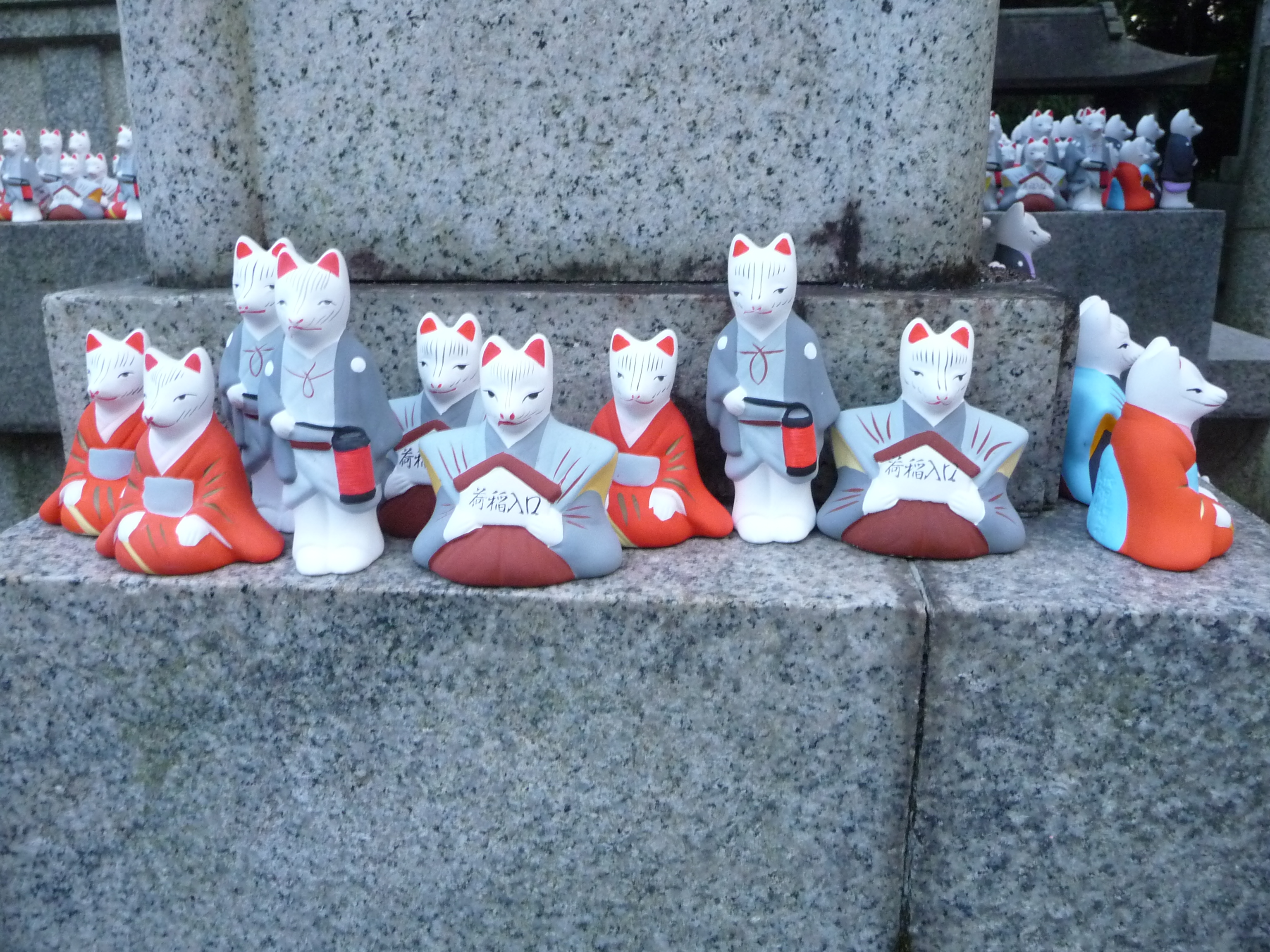 Several statues of white foxes in kimono