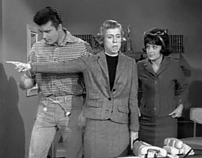 A black and white screenshot from the television series, The Beverly Hillbillies shows Max Baer, Jr. as Jethro, Nancy Kulp as Jane Hathaway, and Sharon Tate as Janet Trego, a secretary. Tate is wearing a business suit and a dark wig, and is watching Miss Hathaway