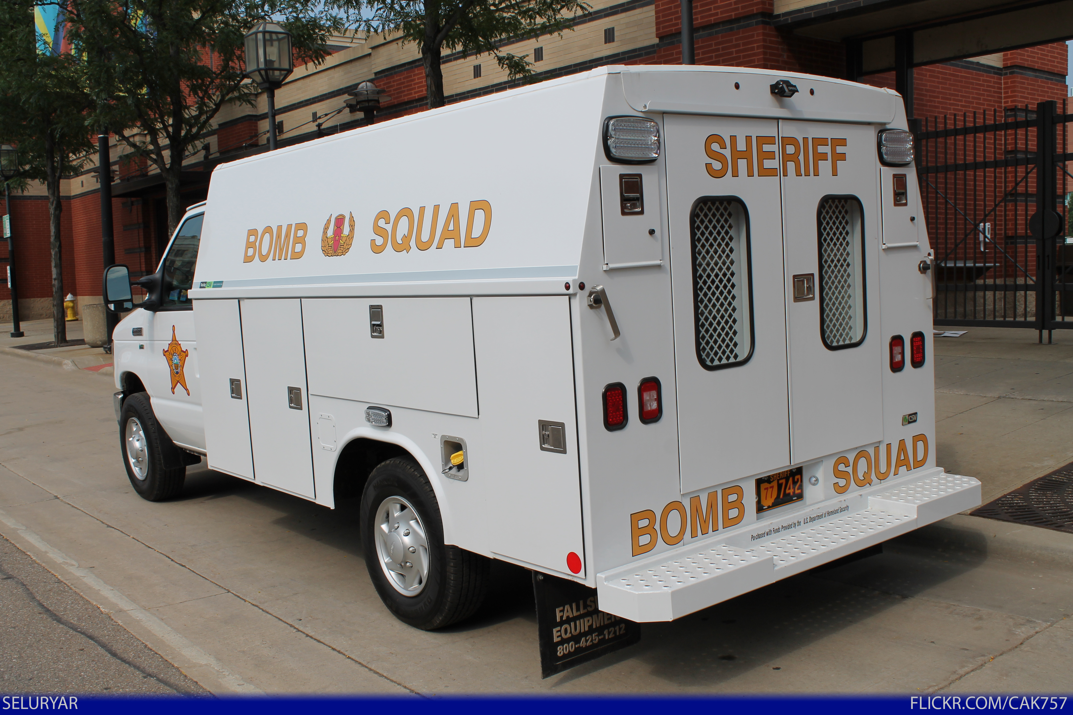 A white, tricked-out Ford E-350 truck labeled bomb squad