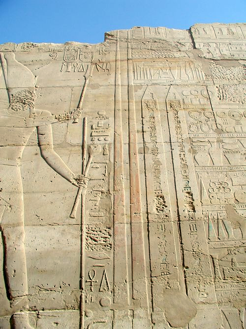 Depiction of Tuthmose III at Karnak holding a Hedj Club and a Sekhem Scepter standing before two obelisks he had erected there. ThutmosesIII-RaisingObelisks-Karnak.png
