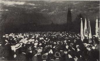 A large crowd, mostly students in typical Swedish white student caps, participating in the traditional Walpurgis Night celebration with song outside the Castle in Uppsala. The silhouette of the cathedral towers may be seen in the background. To the right are banners and standards of the student nations. Image from c. 1920.