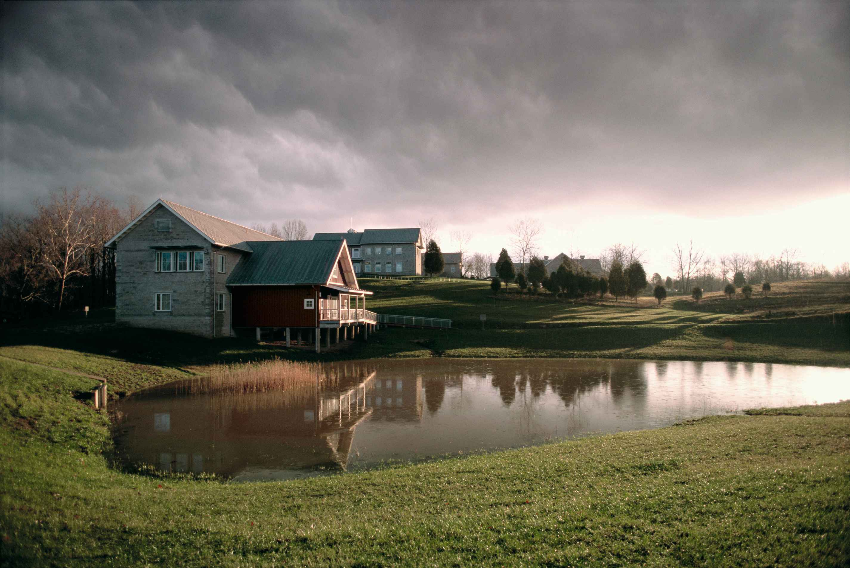 File Building And Pond With Line Of Stormy Clouds Above
