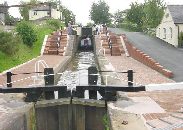 View from the bottom of a series of three locks together, rising up like three big stairs made of water and lockgates.