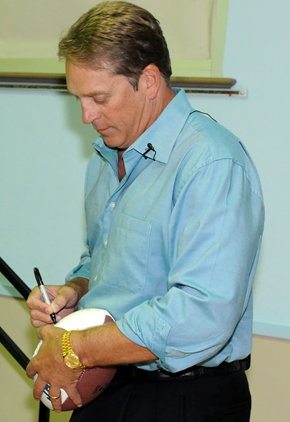 Color full-length photograph of stocky, well-tanned white man (Jack Del Rio), wearing teal blue button-up shirt and black pants while signing a football.