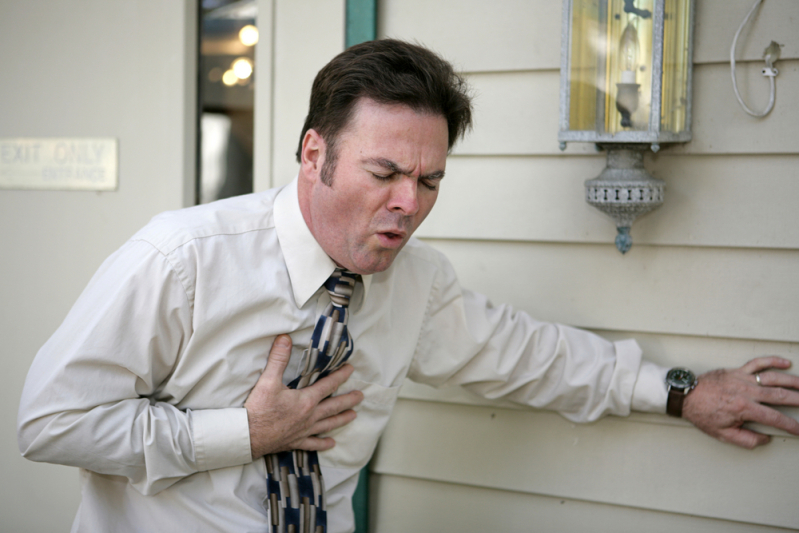 Man coughing with his hand on his chest