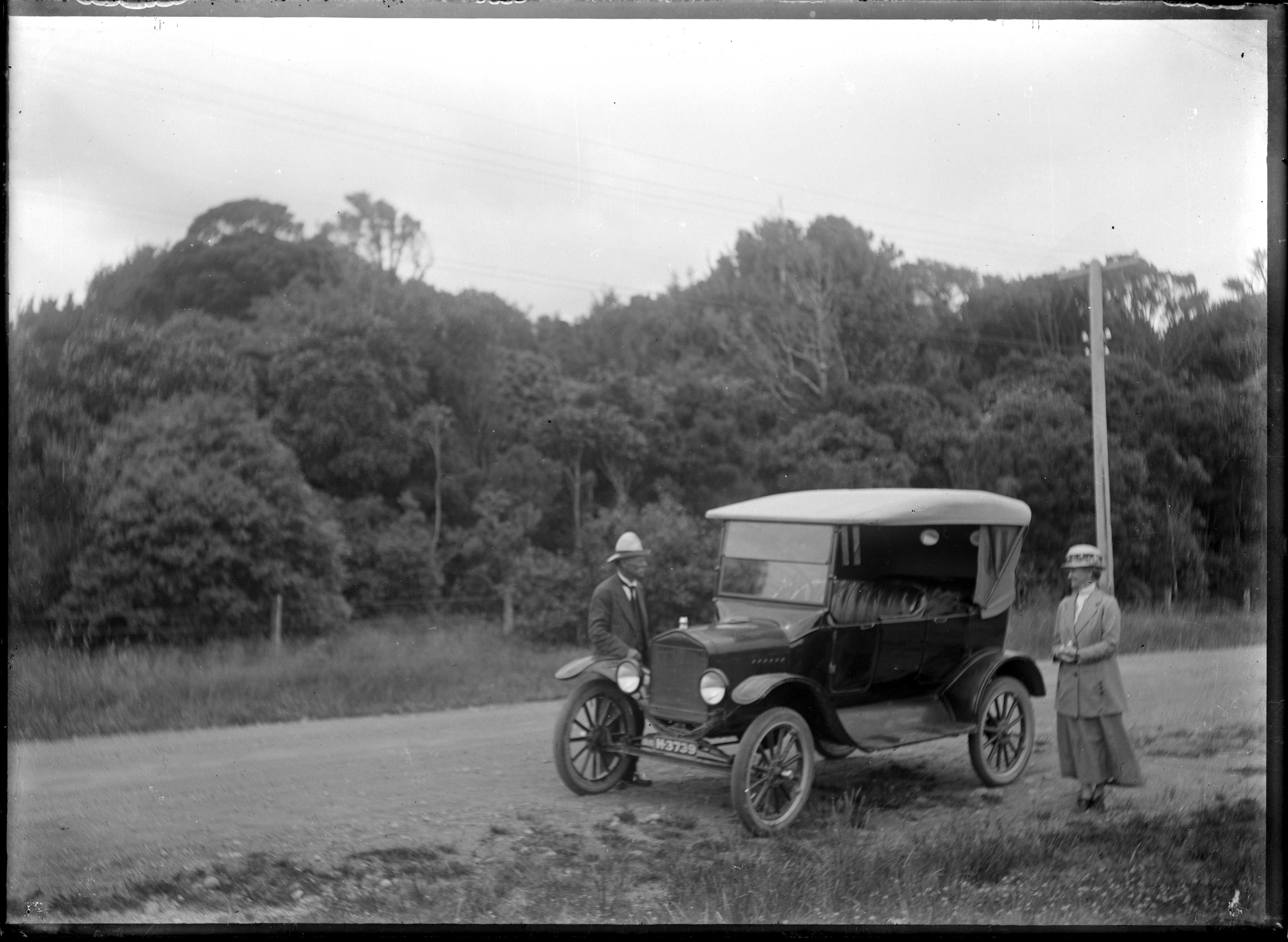 beside a car on a road in a hilly, bushy area ATLIB 324339.png English: Unidentified man and woman standing beside a 1923 Ford Model T Touring Car, on a