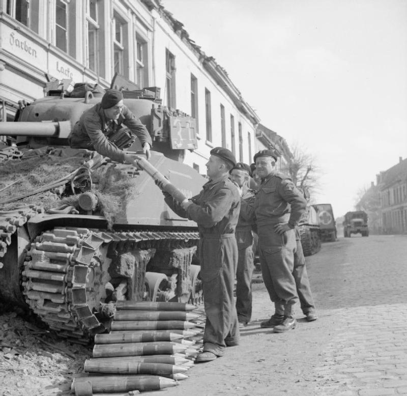 The crew of a Sherman tank loading main gun rounds