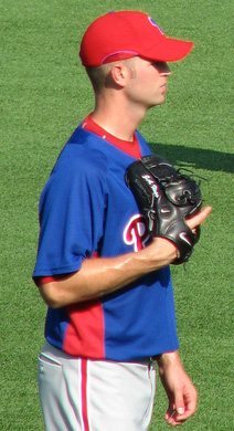 A young man in a blue baseball jersey and red baseball cap holds a black baseball glove against his chest with his left hand