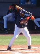 A man in a blue batting helmet and baseball uniform stands in a left-handed batting stance.