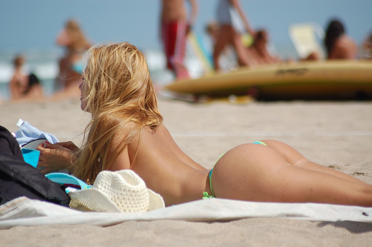 [Image: Topless_blonde_sunbathing_at_the_beach.jpg]