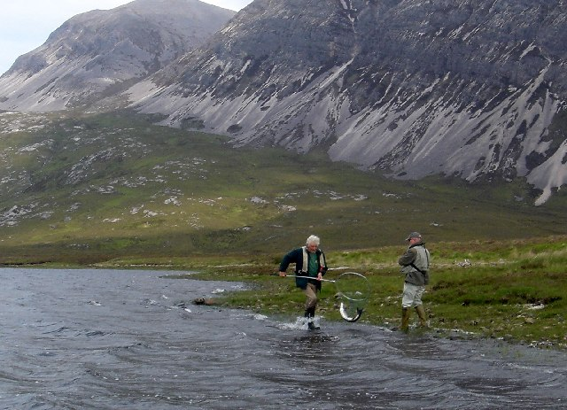 In the net! Angler & Ghillie land a salmon from Loch Stack with Ben Arkle behind