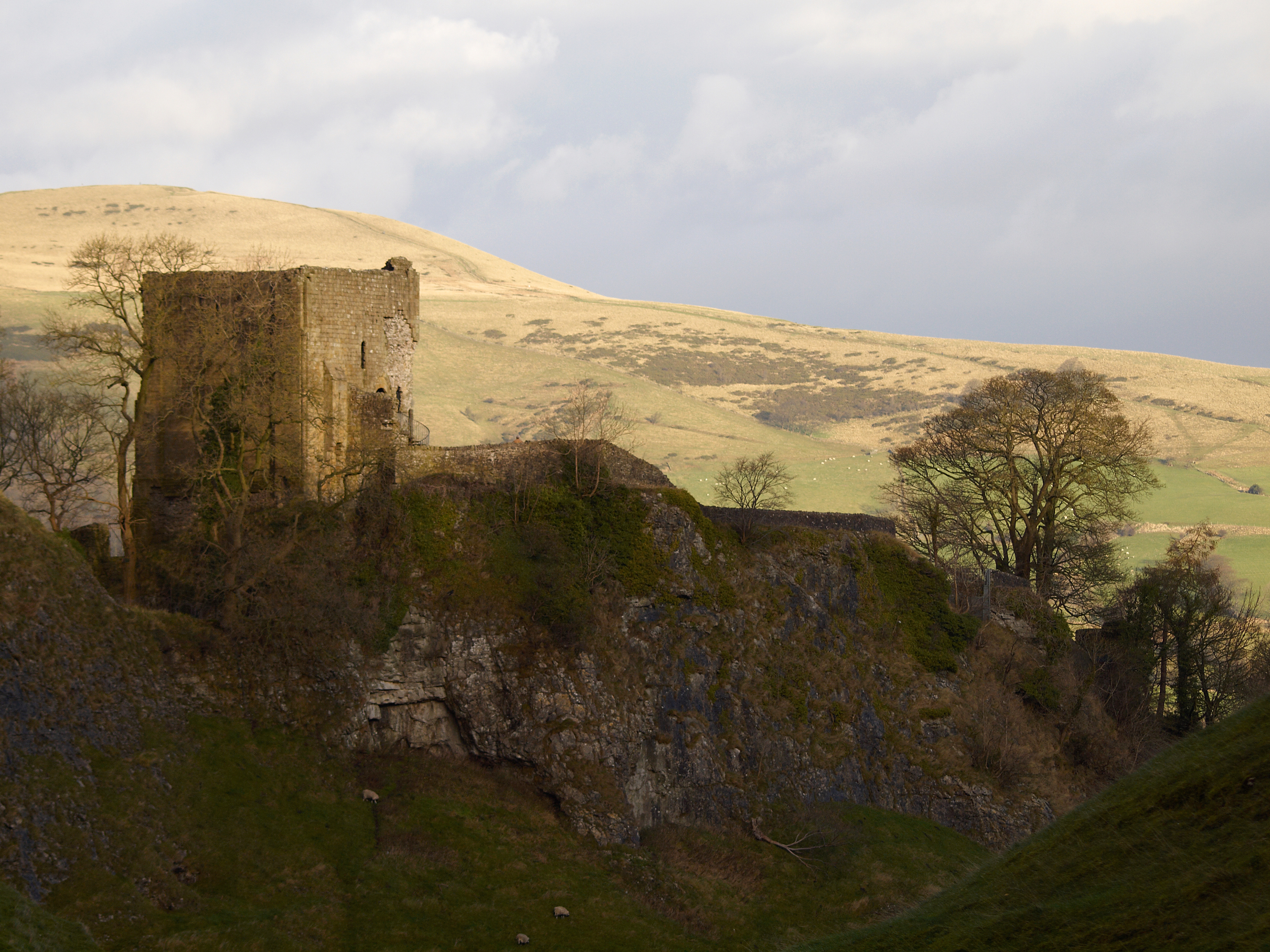A stone tower with a wall running off to the right standing on top of a drop into a gorge. There are hills in the background.