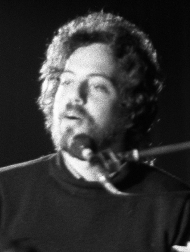 Close-up of Billy Joel singing at the piano in 1972; black and white photo.