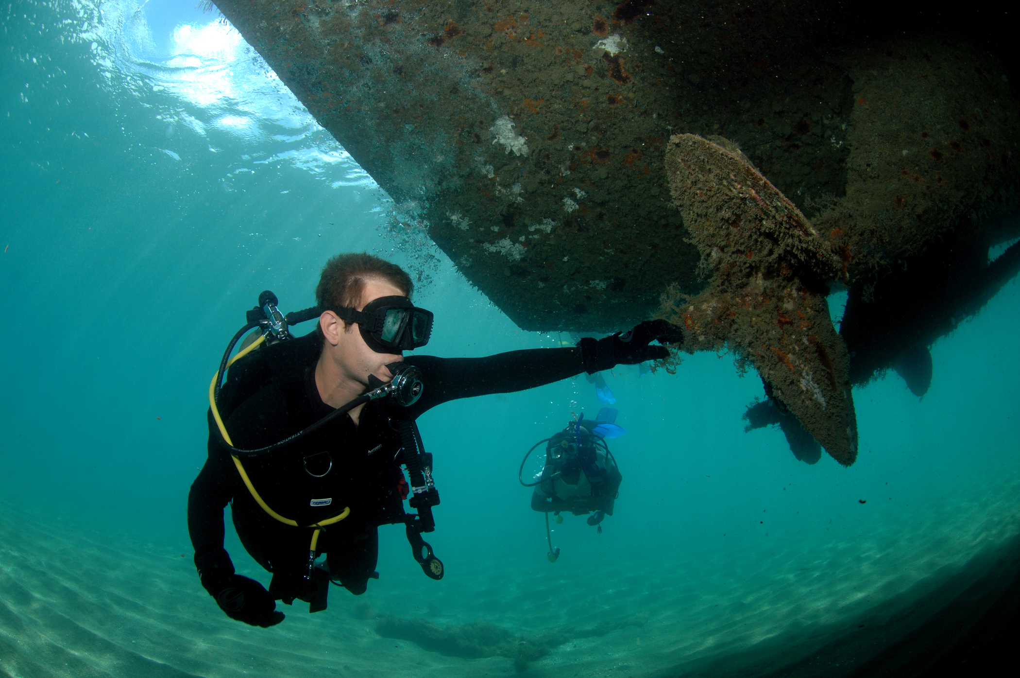 scuba divers near a sunken ship