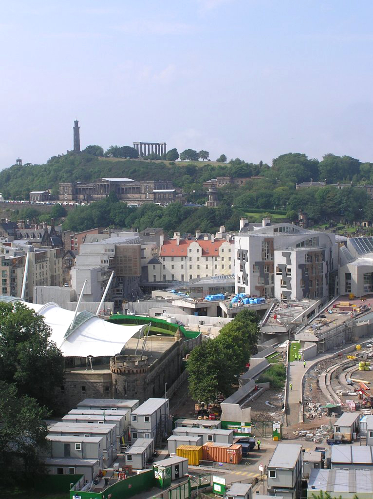 Enric Miralles' Scottish Parliament complex in Holyrood Park during construction. The building was completed in 2004. Above and behind the new Parliament is the neoclassical Royal High School, which was prepared for a previous devolved Scottish parliament, but never used.