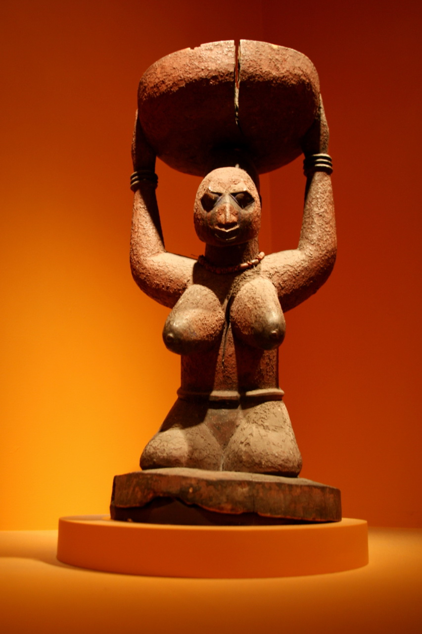 A sculpture of a bare breasted femae torso and head, her arms uplifted to support a bowl balanced atop her head.