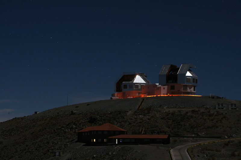 The Magellan Telescope buildings at night, lit by ambient light