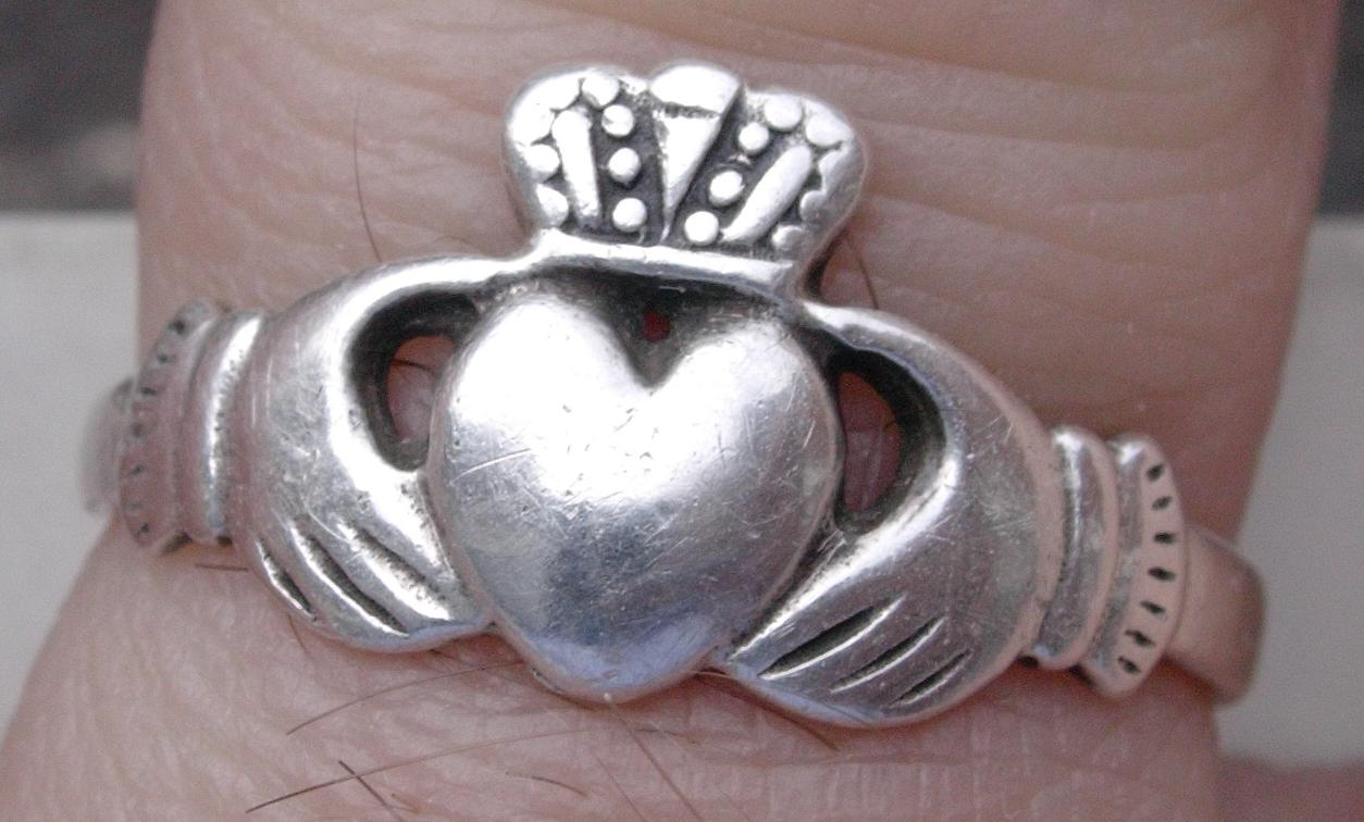Closeup of a Claddagh ring on a finger, an Irish promise or friendship ring with heart hands and crown.