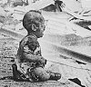 Monochrome photograph of an injured baby sitting alone and crying on the platform of a ruined and smoking railway station