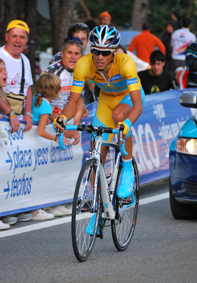 A man in yellow clothes and blue shoes, riding a bicycle, followed by a car. People are watching him from behind a fence.