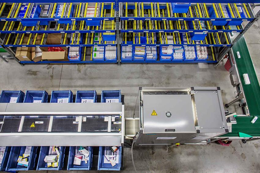 Regale mit Produkten und Laufbändern, sowie Sortiermaschine zur Vorbereitung von Bestellungen