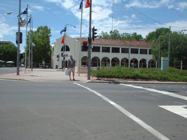 A pedestrian at the intersection of Alinga Street and Northbourne Avenue, Canberra, Australia.