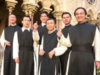 Vietnamese Cistercian monks standing in a cloister and wearing their religious habits