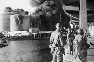 men n quayside looking across water at burning tanks