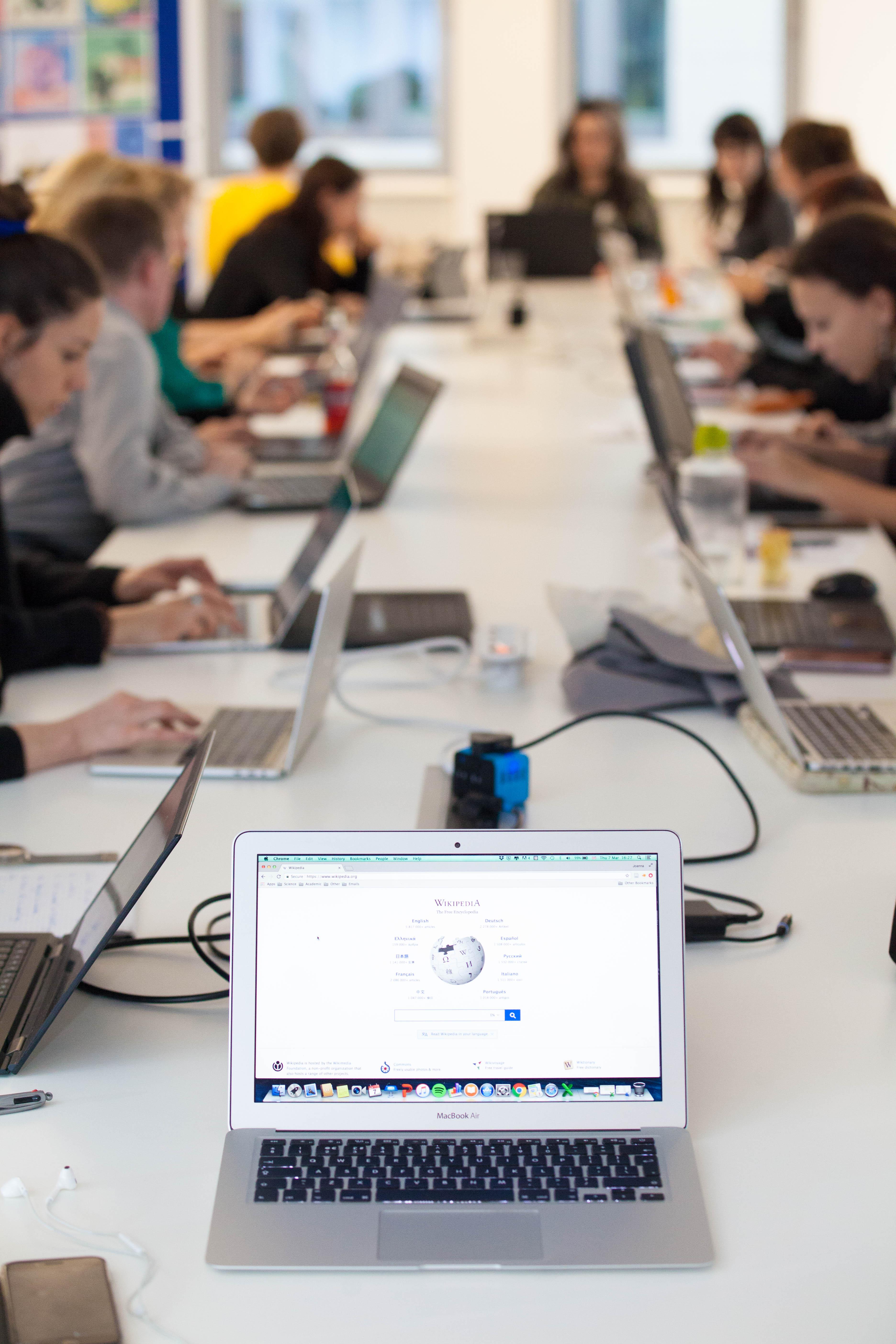 Vista d'una taula amb gent asseguda treballant amb ordinadors portàtils. En primer terme, un ordinador amb la pàgina principal de la Viquipèdia a la pantalla