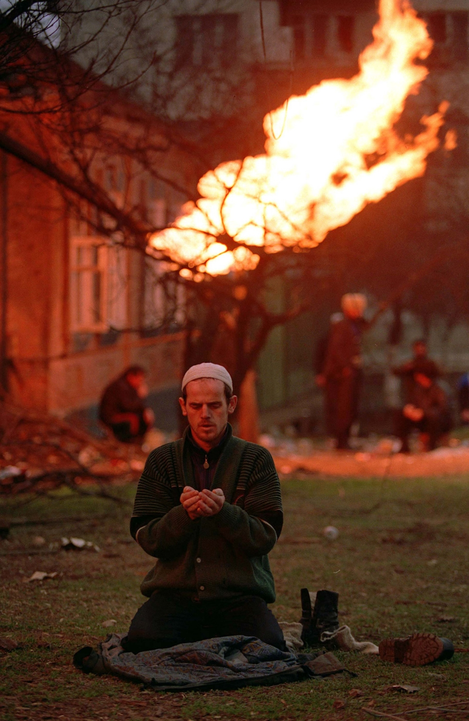 A Chechen civilian prays in Grozny, January 1995. The flame in the background is coming from a gas pipeline which was hit by shrapnel