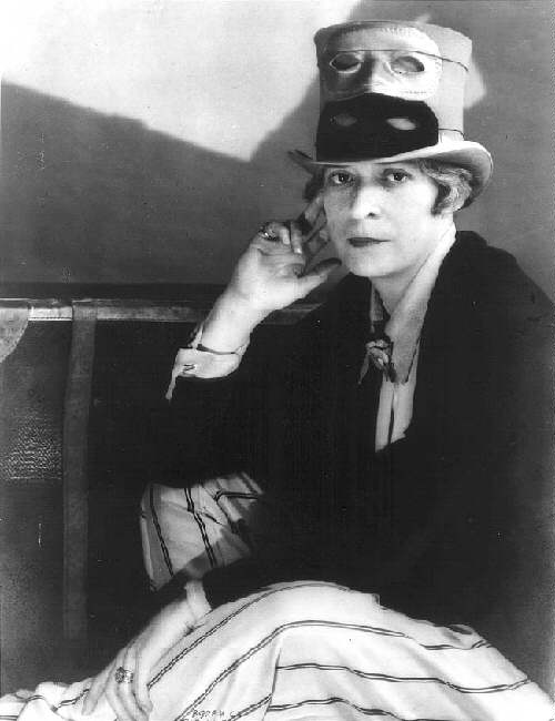 Janet Flanner, right hand touching left side of face with fingers extended, wearing a flared top hat with two masks on the hat, one white, the other black