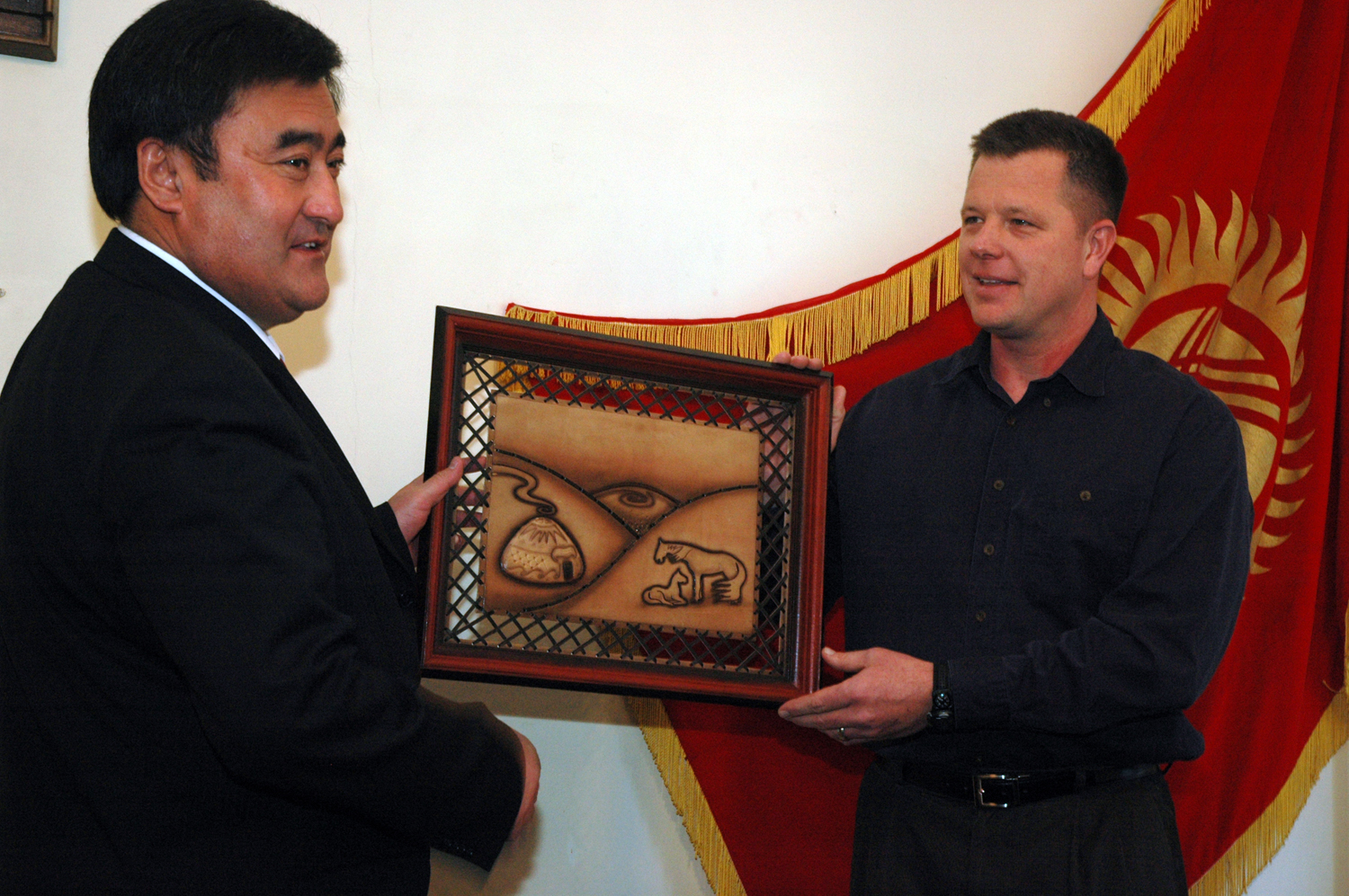 Bishkek mayor Arstanbek Nogoev presents a gift for Colorado Springs mayor Lionel Rivera to a US airman at Manas Air Base, in a ceremony aimed at reviving ties between the two sister cities<!-- citation -->