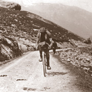 A man on a bicycle, riding on a mountain road.