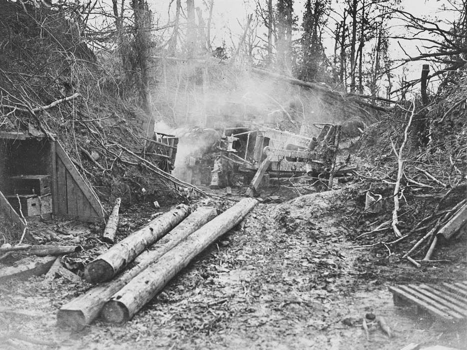 German dugout at Bourlon Wood, France, September 1918. Part of Bourlon Wood after its capture by the Canadian Corps on 27 September 1918. To the left is the wood-lined entrance to a German dugout. In the centre there are the burning remains of a German heavy gun, identified in the caption as a Howitzer.The attack on Bourlon Wood was the beginning of the Cambrai offensive, a highly successful thrust towards the German Hindenburg Line by the British First and Third Armies. Bourlon Wood was captured by the Canadian Corps under the command of General Sir Arthur Currie (1875-1933). [Original reads: 'A Dug-out fire in Bourlon Wood. An 8.3 German Howitzer blown over by the explosion of a dump near it. Good Canadian artillery fire is sure proof here.'] http://digital.nls.uk/74549246
