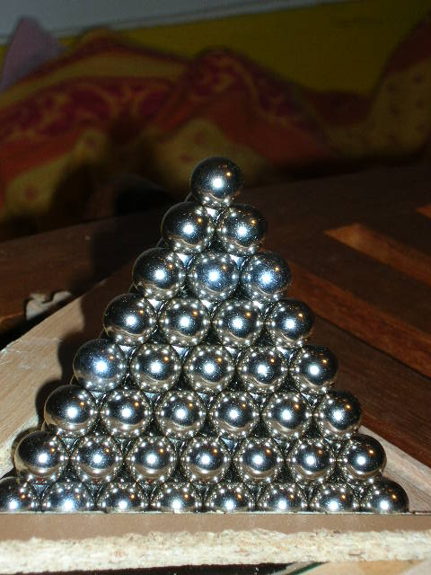 A shiny pyramid of tightly packed ball bearings.