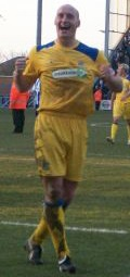A bald man wearing yellow football shirt, shorts and socks and black football boots. He is smiling broadly and clenching his fists. He is standing on a grass surface and several people and indistinct structures are behind him.