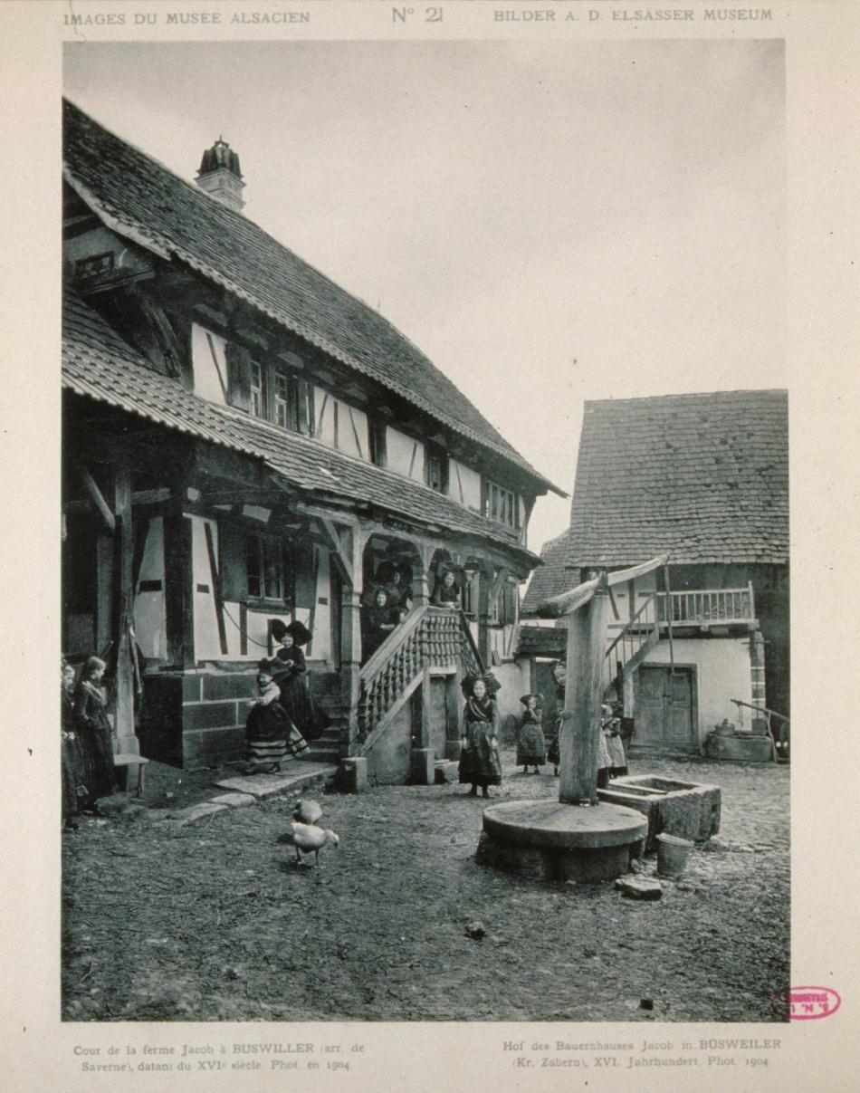 Par Musée Alsacien de Strasbourg : Cour de la ferme de Jacob à Buswiller en 1904 http://opac.bnu.fr/id=1:668358 — Bibliotheque Nationale et Universitaire de Strasbourg (BNU), CC BY-SA 3.0, https://commons.wikimedia.org/w/index.php?curid=19037721