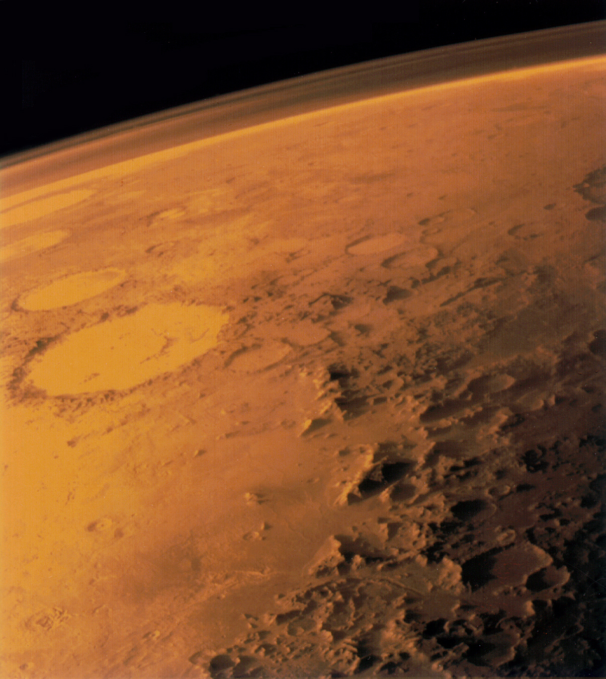 Marss thin atmosphere, visible on the horizon in this low-orbit photo.