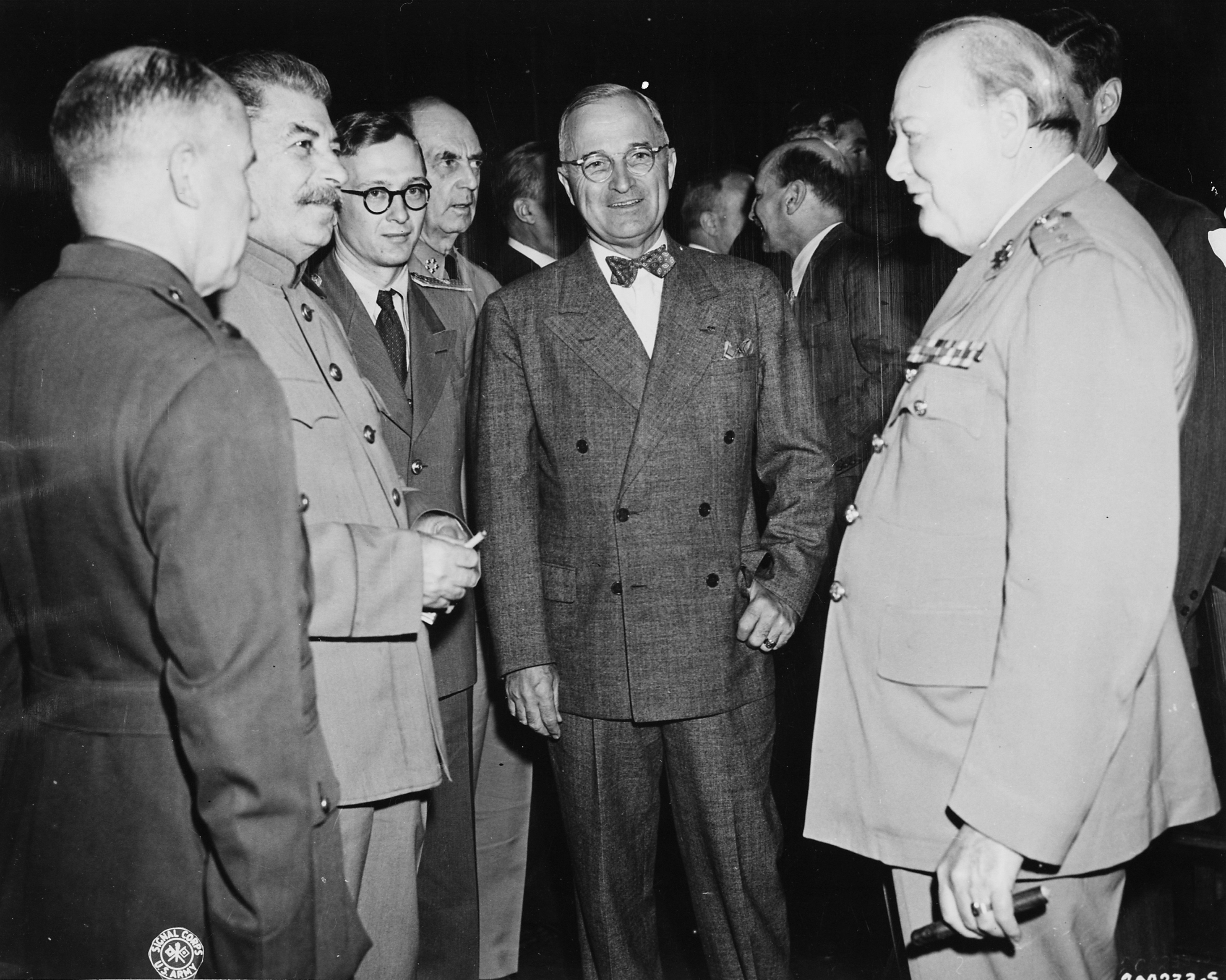 Three men in suits standing with several men in the background