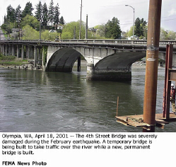 The Fourth Avenue Bridge in Olympia was severely damaged. In the fore-ground is a piling for a temporary bridge.