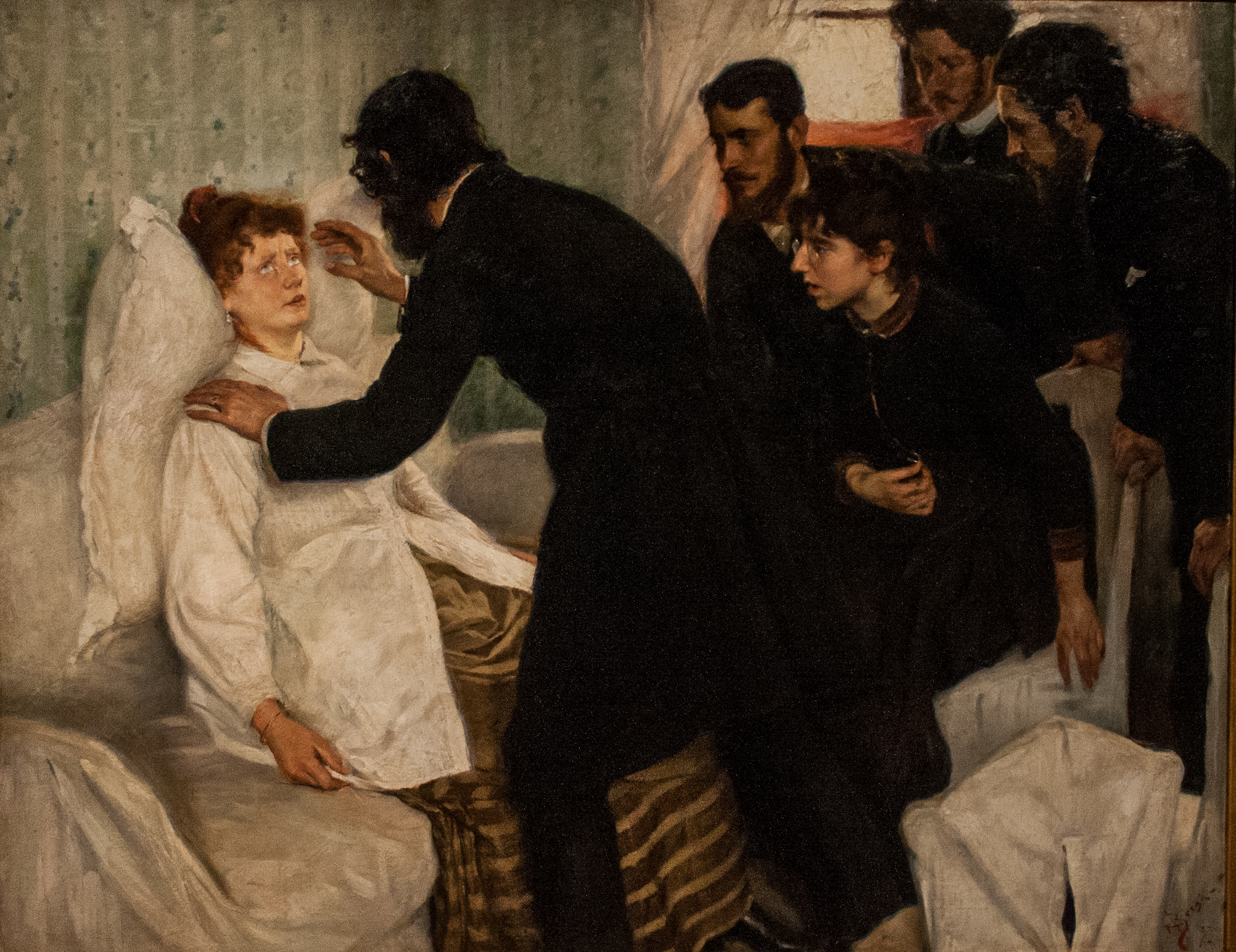 Painting shows a man in dark clothing (facing away from us), leaning over a woman in a white jacket and striped dress. He has one hand on her shoulder and is holding the other before her face; her eyes are rolled up and she is lying against a pillow. Several men and boys in dark clothes look on. Hypnotic Séance by Richard Bergh in the Nationalmuseum, Stockholm. 1887. Public Domain.