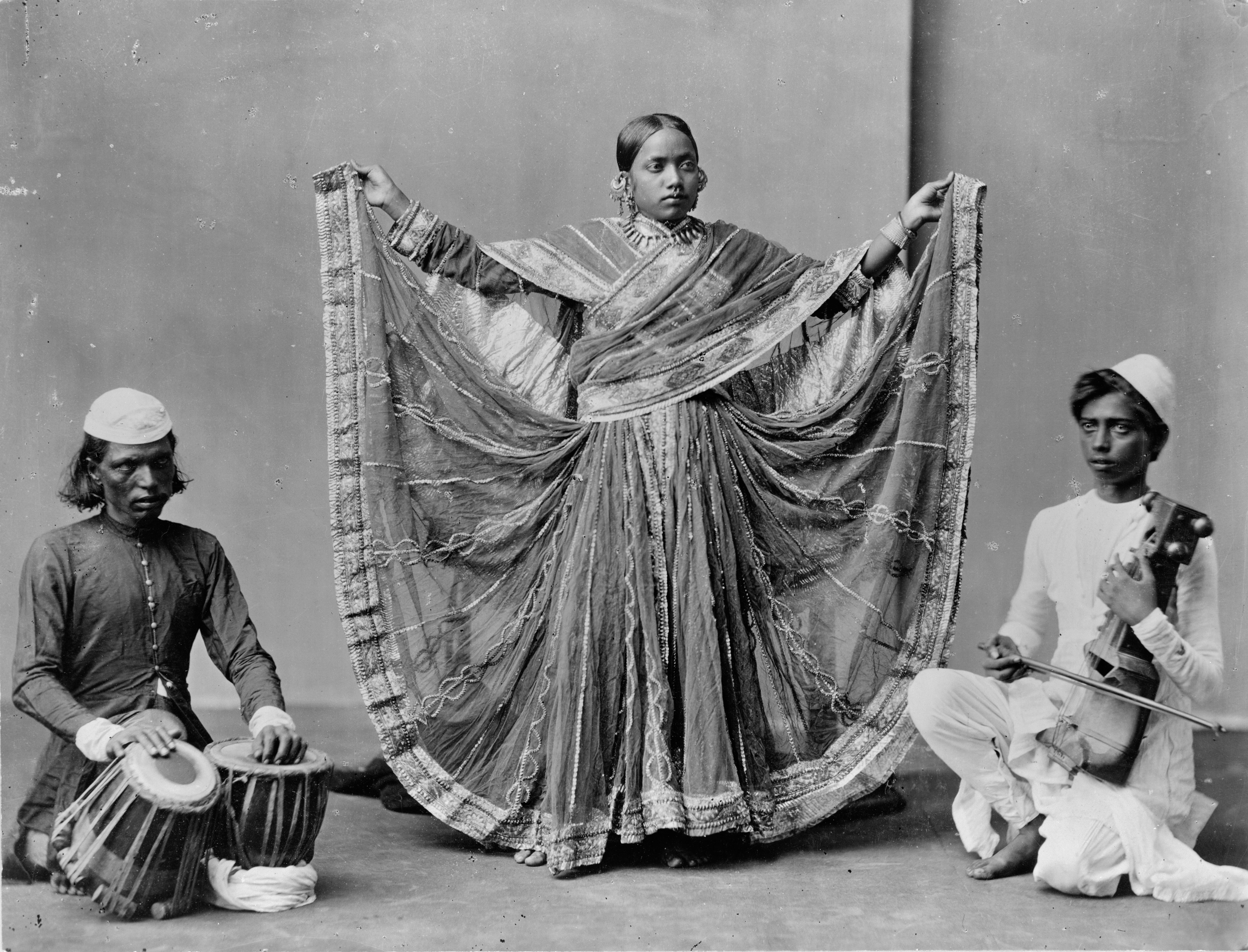 Photo shows a female dancer standing between two musicians, one with drums and the other with a stringed instrument. Physical description: 1 photographic print.